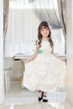 Reizendes kleines Mädchen, das im weißen eleganten Kleid aufwirft Stockbild