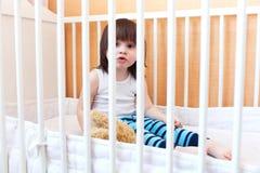 Reizendes Kleinkind, das im weißen Bett sitzt Stockfotos