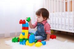 Reizendes Kleinkind, das zu Hause Erbauer spielt Stockfotos
