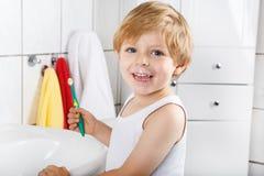 Reizendes Kleinkind mit blauen Augen und blonden dem Haar, die seine Zähne putzt Lizenzfreies Stockbild