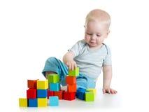 Reizendes Kleinkindbaby, das mit Gebäudewürfeln spielt Lokalisiert auf Weiß lizenzfreie stockfotos