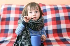 Reizendes krankes Kleinkind im warmen woolen Schal und in der Tasse Tee Lizenzfreies Stockfoto