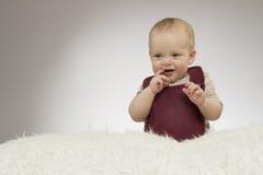 Reizendes Lächeln des kleinen Jungen, sitzend auf der weißen Decke, Atelieraufnahme, lokalisiert auf grauem Hintergrund, lustiges Lizenzfreies Stockbild
