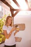 Reizendes lächelndes blondes Mädchen, das Mobiltelefon betrachtet Lizenzfreie Stockbilder