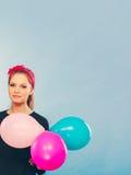 Reizendes lächelndes Mädchen hält bunte Ballone Lizenzfreies Stockfoto