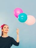 Reizendes lächelndes Mädchen hält bunte Ballone Lizenzfreie Stockbilder