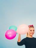 Reizendes lächelndes Mädchen hält bunte Ballone Stockbild