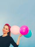 Reizendes lächelndes Mädchen hält bunte Ballone Lizenzfreie Stockfotos