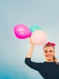 Reizendes lächelndes Mädchen hält bunte Ballone Lizenzfreie Stockfotografie