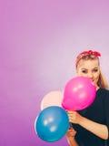 Reizendes lächelndes Mädchen hält bunte Ballone Stockfotos