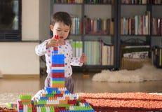 Reizendes lachendes kleines Kind, Brunettemädchen des Vorschulalters spielend mit den bunten Blöcken, die auf einem Boden sitzen Lizenzfreies Stockfoto