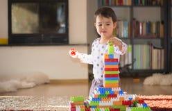 Reizendes lachendes kleines Kind, Brunettemädchen des Vorschulalters spielend mit den bunten Blöcken, die auf einem Boden sitzen Stockbild