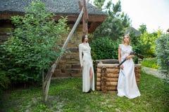 Reizendes Mädchen im weißen Kleid, das mit einem Jagdgewehr aufwirft lizenzfreies stockbild
