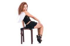 Reizendes Mädchen, das auf einem Stuhl sitzt stockbilder