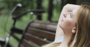 Reizendes Mädchen, das auf einer Bank im Park im Sommer stillsteht lizenzfreie stockfotos