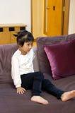 Reizendes Mädchen, das auf Sofa sitzt Stockbild