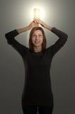 Reizendes Mädchen, das eine Leuchtstofflampe über seinem Kopf hält Stockfotografie