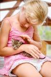 Reizendes Mädchen, das eine schöne kleine Katze streichelt Stockbild