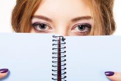 Reizendes Mädchen, das hinter Notizbuch sich versteckt Stockbild