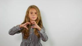 Reizendes Mädchen mit dem langen gewellten Haar macht Herz durch Hände Zeichen der Liebe stock video footage
