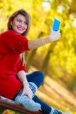 Reizendes Mädchen mit dem Smartphone, der selfie Foto macht Lizenzfreie Stockfotos
