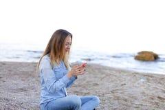 Reizendes Mädchen rattert am Telefon mit Lächeln und sitzt auf Strand n Lizenzfreies Stockbild