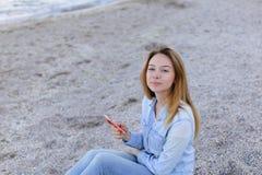 Reizendes Mädchen rattert am Telefon mit Lächeln und sitzt auf Strand n Stockfoto