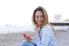 Reizendes Mädchen rattert am Telefon mit Lächeln und sitzt auf Strand n Stockfotografie