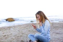 Reizendes Mädchen rattert am Telefon mit Lächeln und sitzt auf Strand n Lizenzfreie Stockfotografie