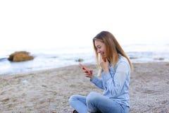 Reizendes Mädchen rattert am Telefon mit Lächeln und sitzt auf Strand n Lizenzfreies Stockfoto