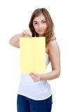 Reizendes Mädchen zeigt ein unbelegtes Blatt A4 des Gelbs Stockfotografie