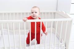 Reizendes 6-monatiges Baby, das im weißen Bett steht Stockfoto