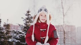 Reizendes Nahaufnahmeporträt des netten kleinen kaukasischen Mädchens im Winter kleidet werfenden Schnee in der Luft, die Spaßzei stock footage