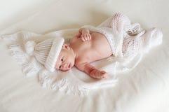 Reizendes neugeborenes Alter von 2 Wochen in der weißen Strickmütze Stockfotografie