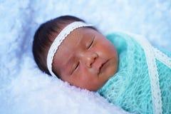 Reizendes neugeborenes Mädchen, das auf weißer Decke schläft stockbild