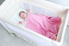 Reizendes neugeborenes Mädchen schläft in der Reisekrippe Stockfotografie