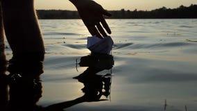 Reizendes Papierboot wird von einem Jungen in einem See bei Sonnenuntergang in SlomO gestartet stock video
