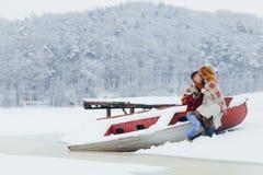 Reizendes Porträt im Freien der netten küssenden Paare beim Sitzen auf dem Boot nahe dem gefrorenen Fluss Das rote Haar Lizenzfreies Stockfoto