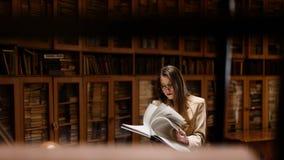 Reizendes stilvolles Studentenmädchen, das in der Bibliothek studiert lizenzfreies stockfoto
