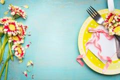 Reizendes Tabellengedeck mit Blumen, Platte, Tischbesteck und Papierkarte mit rosa Band, auf schäbigem schickem Hintergrund des T Lizenzfreies Stockfoto