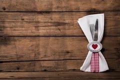 Reizendes Tischbesteck im Rot im Weiß überprüfte mit Herzen und einer Serviette O Lizenzfreie Stockbilder