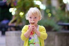 Reizendes Vorschülermädchen, das draußen Eiscreme isst Lizenzfreie Stockbilder