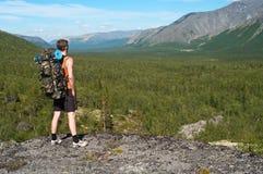 Reiziger in berg die zich op piek bevindt stock fotografie