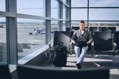 Reiziger die laptop in luchthaventerminal met behulp van royalty-vrije stock afbeelding