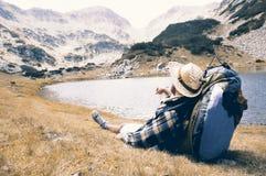 Reiziger die van de mening genieten en bij bergplaats ontspannen stock fotografie