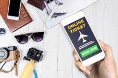 Reiziger die zijn mobiele telefoon met behulp van aan het kaartje van de boekvlucht royalty-vrije stock fotografie