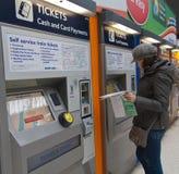Reiziger het kopen treinkaartjes stock foto's