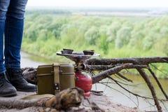 Reiziger in het verblijf van leerlaarzen over een klip boven de rivier dichtbij stock afbeelding
