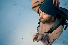 Reiziger met kompas in de winterbos Stock Foto's