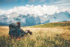 Reiziger met rugzak ontspannende zitting op grasvallei bij bergen royalty-vrije stock afbeeldingen